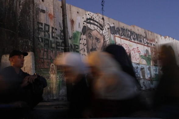 Palestinian women walk past an Israeli security officer as they cross at Qalandiya checkpoint outside the West Bank city of Ramallah on the fourth Friday of the holy month of Ramadan August 10, 2012. REUTERS/Mohamad Torokman