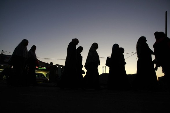 Palestinian women walk towards an Israeli checkpoint on their way to pray at the Al-Aqsa Mosque in Jerusalem, on the last Friday off the Muslim holy month of Ramadan near the West Bank city of Ramallah, Friday, Aug. 17, 2012.(AP Photo/Majdi Mohammed)