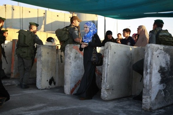 A Palestinian woman passes through an Israeli checkpoint on her way to pray at the Al-Aqsa Mosque in Jerusalem, on the last Friday of the Muslim holy month of Ramadan near the West Bank city of Ramallah, Friday, Aug. 17, 2012.(AP Photo/Majdi Mohammed)