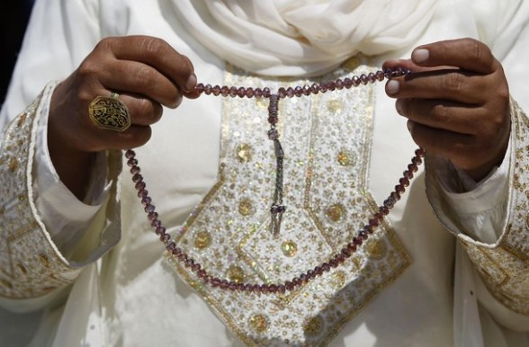 A Palestinian woman holds prayers beads on the compound known to Muslims as Noble Sanctuary and to Jews as Temple Mount in Jerusalem's Old City, on the last Friday of the holy month of Ramadan August 17, 2012.   REUTERS/Ammar Awad