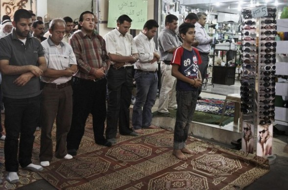 Palestinian Muslim worshippers pray next to shops in a the market after they were prevented from attending a prayer for the Islamic holy month of Ramadan in an over-crowded nearby mosque, in the West Bank town of Nablus Thursday Aug. 2, 2012. (AP Photo/Nasser Ishtayeh)