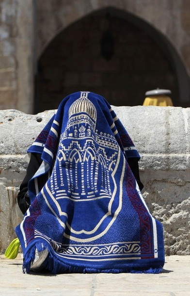 A Palestinian woman, covered in a prayer mat to protect herself from the sun, reads the Koran on the compound known to Muslims as Noble Sanctuary and to Jews as Temple Mount during the holy month of Ramadan in Jerusalem's Old City August 3, 2012. REUTERS/Ammar Awad