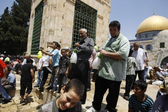Palestinian men spray water on people to cool them down near the Dome of the Rock (R), on the compound known to Muslims as Noble Sanctuary and to Jews as Temple Mount, during the holy month of Ramadan in Jerusalem's Old City, August 3, 2012. REUTERS/Ammar Awad