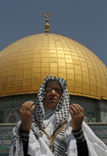 A Palestinian Muslim woman prays outside the Dome of the Rock at the Al-Aqsa mosque compound in Jerusalem during the third Friday prayers of Islam's holy month of Ramadan on August 3, 2012. Muslims fasting in the month of Ramadan must abstain from food, drink and sex from dawn until sunset, when they break the fast with the meal known as Iftar. AFP PHOTO/MUSA AL SHAER