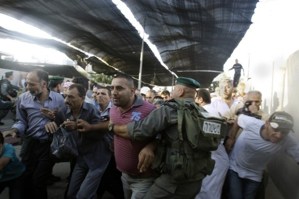Palestinian men pass an Israeli checkpoint on their way to pray at the Al-Aqsa Mosque in Jerusalem, on the third  Friday of the Muslim holy month of Ramadan near Bethlehem, West Bank, Friday, Aug. 03, 2012. Ramadan is the ninth month of the Muslim year which lasts 30 days, during which strict fasting is observed from sunrise to sunset. (AP Photo/Nasser Shiyoukhi)