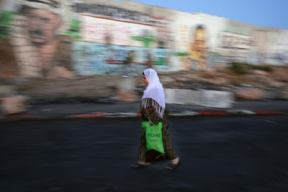 A Palestinian woman walk towards an Israeli checkpoint on her way to pray at the Al-Aqsa Mosque in Jerusalem, on the third Friday of the Muslim holy month of Ramadan near Ramallah, West Bank, Friday, Aug. 3, 2012. Ramadan is the ninth month of the Muslim year which lasts 30 days, and is devoted to dawn-to-dusk fasting, prayers and good deeds. (AP Photo/Majdi Mohammed)