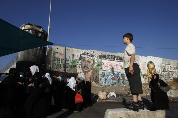 A Palestinian boy watch as women walk in front of a section of Israel's controversial barrier near Qalandiya checkpoint outside the West Bank city of Ramallah, on the third Friday of the holy month of Ramadan August 3, 2012. REUTERS/Baz Ratner