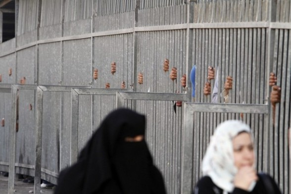 Palestinian women pass through an Israeli checkpoint on their way to pray at the Al-Aqsa Mosque in Jerusalem, on the Third  Friday of the Muslim holy month of Ramadan near Bethlehem, West Bank, Friday, Aug. 03, 2012. Ramadan is the ninth month of the Muslim year which lasts 30 days, and is devoted to dawn-to-dusk fasting, prayers and good deeds. (AP Photo/Nasser Shiyoukhi)