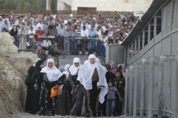 Palestinian women pass an Israeli checkpoint on their way to pray at the Al-Aqsa Mosque in Jerusalem, on the third  Friday of the Muslim holy month of Ramadan near Bethlehem, West Bank, Friday, Aug. 03, 2012. Ramadan is the ninth month of the Muslim year which lasts 30 days, and is devoted to dawn-to-dusk fasting, prayers and good deeds. (AP Photo/Nasser Shiyoukhi)