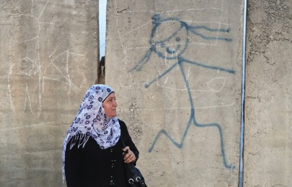 A Palestinian woman walks in front of a section of Israel's controversial barrier near Qalandiya checkpoint outside the West Bank city of Ramallah, on the third Friday of the holy month of Ramadan August 3, 2012. REUTERS/Baz Ratner
