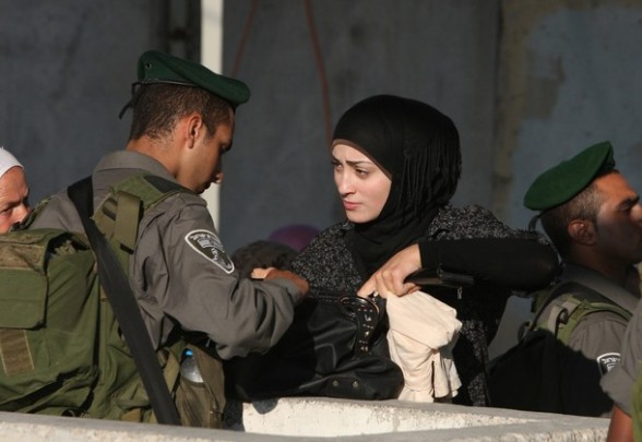 An Israeli border policeman checks the bag of a Palestinian woman as Muslim worshipers wait to cross the Qalandia checkpoint between Ramallah and Jerusalem on their way to the al-Aqsa mosque compound for the third Friday prayer of Ramadan on August 3, 2012. AFP PHOTO/ABBAS MOMANI