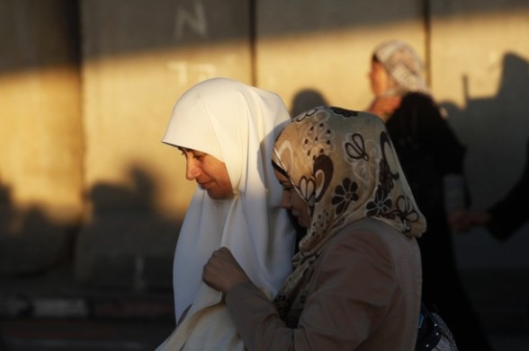 Palestinian women walk in front of a section of Israel's controversial barrier near Qalandiya checkpoint outside the West Bank city of Ramallah, on the third Friday of the holy month of Ramadan August 3, 2012. REUTERS/Baz Ratner