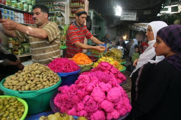 Shop vendors sell vegetables at a market in the old city of the West bank town of Hebron, during the Muslim holy month of Ramadan on August 4, 2012. Muslims fasting in the month of Ramadan must abstain from food, drink and sex from dawn until sunset, when they break the fast with the meal known as Iftar.  AFP PHOTO / HAZEM BADER