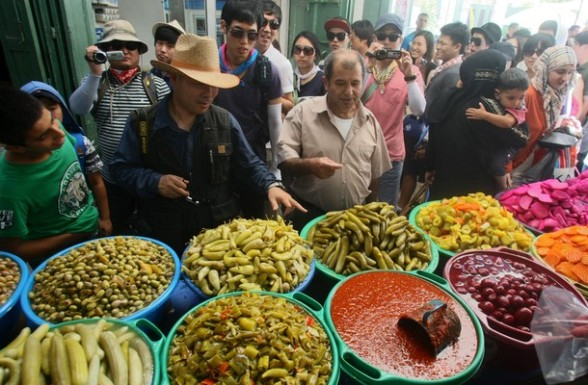 Tourists look at vegetables for sale in the old city of the West bank town of Hebron, during the Muslim holy month of Ramadan on August 4, 2012. Muslims fasting in the month of Ramadan must abstain from food, drink and sex from dawn until sunset, when they break the fast with the meal known as Iftar.  AFP PHOTO / HAZEM BADER