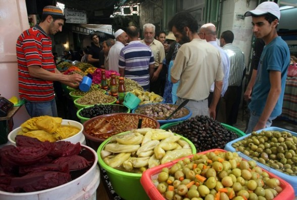 Shoppers walk past a vegetable vendor at a market in the old city of the West bank town of Hebron, during the Muslim holy month of Ramadan on August 4, 2012. Muslims fasting in the month of Ramadan must abstain from food, drink and sex from dawn until sunset, when they break the fast with the meal known as Iftar.  AFP PHOTO / HAZEM BADER