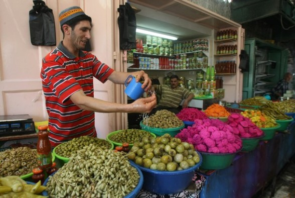 A shop vendor splashes water on his vegetables in the old city of the West bank town of Hebron, during the Muslim holy month of Ramadan on August 4, 2012. Muslims fasting in the month of Ramadan must abstain from food, drink and sex from dawn until sunset, when they break the fast with the meal known as Iftar.  AFP PHOTO / HAZEM BADER