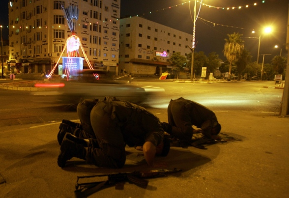 JENIN:Palestinian security forces perform the  dawn prayer in the street during a patrol on the first day of Ramadan in the West Bank city of Jenin  on July 20 2012.