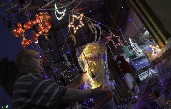 A Palestinian vendor decorates his shop in the West Bank city of Jenin on the eve of the Muslim holy month of Ramadan, Thursday,  July 19, 2012. Muslims throughout the world are preparing to celebrate the holy fasting month of Ramadan, a period devoted to dawn-to-dusk fasting, prayers and spiritual introspection. (AP Photo/Mohammed Ballas)