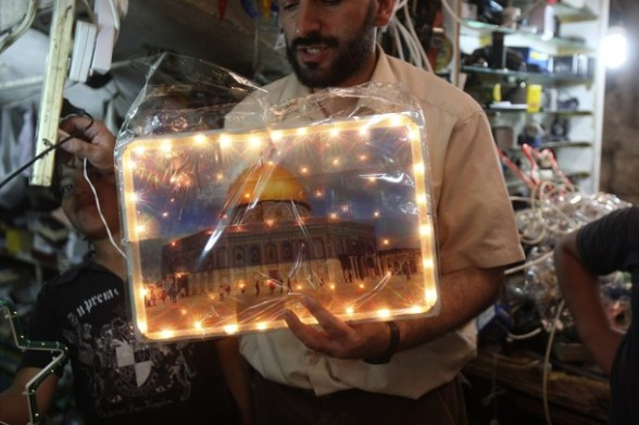 A Palestinian  buys a photograph of the al-Aqsa mosque  at a market in the West Bank city of Nablus,Thursday, July 19, 2012. Ramadan, the holiest month in the Islamic calendar, is expected to begin on Friday. (AP Photo/Nasser Ishtayeh)