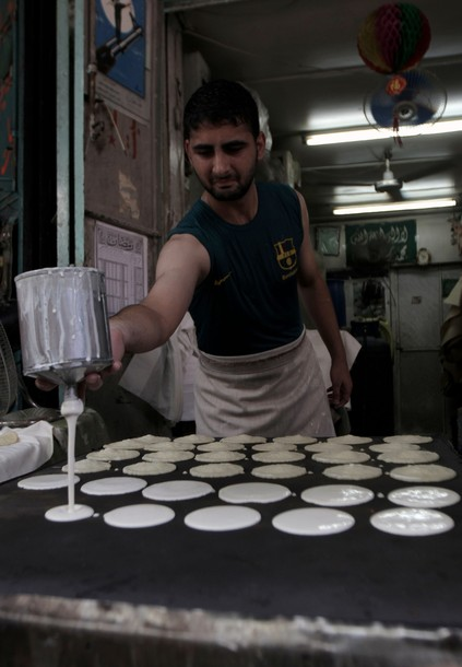 "A Palestinian baker prepares ""Qatayef"", traditional pancakes that are popular during the Muslim fasting month of Ramadan, in Gaza City, on the first day of Ramadan on July 20, 2012. During the lunar month of Ramadan, Muslims fast from dawn to dusk and strive to be more pious and charitable. AFP PHOTO/ SAID KHATIB"