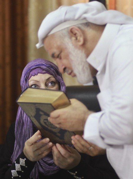 Palestinian Sheik Salem Salama presents a copy of the Koran to Anne Kennedy (L), 49, at the headquarters of the Palestinian Muslim Scholars association in Gaza City July 21, 2012. British citizen Kennedy, who studies and teaches religion in London, announced her conversion to Islam in a news conference in Gaza during the holy month of Ramadan. REUTERS/Mohammed Salem