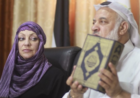 Palestinian Sheik Salem Salama holds a copy of the Koran before presenting it to Anne Kennedy (L), 49, at the headquarters of the Palestinian Muslim Scholars association in Gaza City July 21, 2012. British citizen Kennedy, who studies and teaches religion in London, announced her conversion to Islam in a news conference in Gaza during the holy month of Ramadan. REUTERS/Mohammed Salem