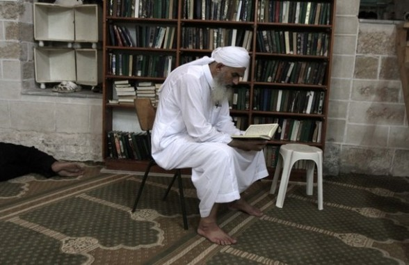 A Palestinian man reads the Koran, Islam's holy book, in al-Omari mosque in Gaza City on the first day of the Muslim fasting month of Ramadan on July 20, 2012. During the lunar month of Ramadan, Muslims fast from dawn to dusk and strive to be more pious and charitable. AFP PHOTO/ SAID KHATIB