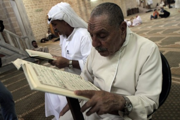 Palestinian men read the Koran, Islam's holy book, in al-Omari mosque in Gaza City on the first day of the Muslim fasting month of Ramadan on July 20, 2012. During the lunar month of Ramadan, Muslims fast from dawn to dusk and strive to be more pious and charitable. AFP PHOTO/ SAID KHATIB