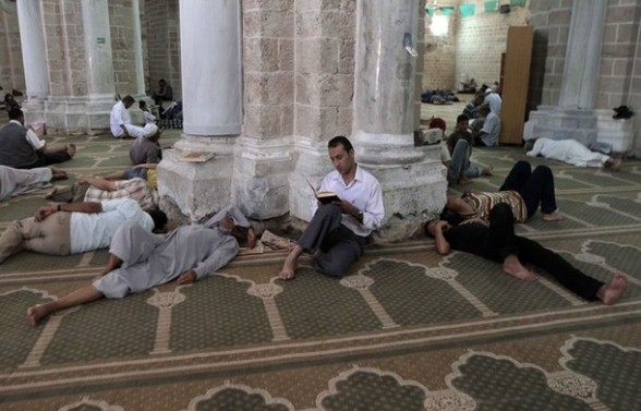 Palestinians rest as a man reads the Koran, Islam's holy book, in al-Omari mosque in Gaza City on the first day of the Muslim fasting month of Ramadan on July 20, 2012. During the lunar month of Ramadan, Muslims fast from dawn to dusk and strive to be more pious and charitable. AFP PHOTO/ SAID KHATIB