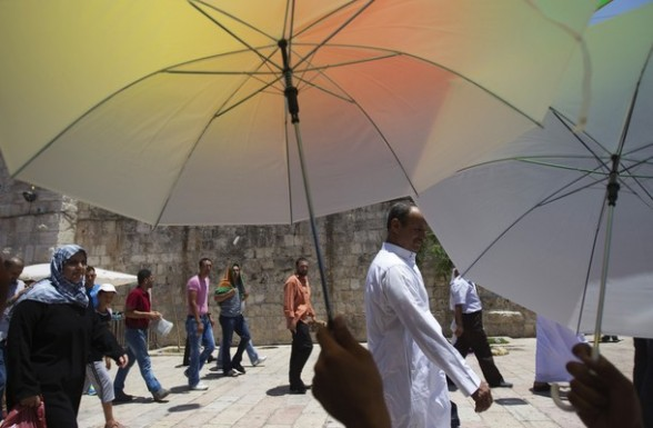 A vendor sells parasols as Palestinians make their way to the compound known to Muslims as Noble Sanctuary and to Jews as Temple Mount in Jerusalem's Old City on the first Friday of the holy month of Ramadan July 20, 2012. Israeli police said that Palestinian males over the age of 40 would be freely permitted to enter the compound Jerusalem's Old City on Friday. REUTERS/Ronen Zvulun