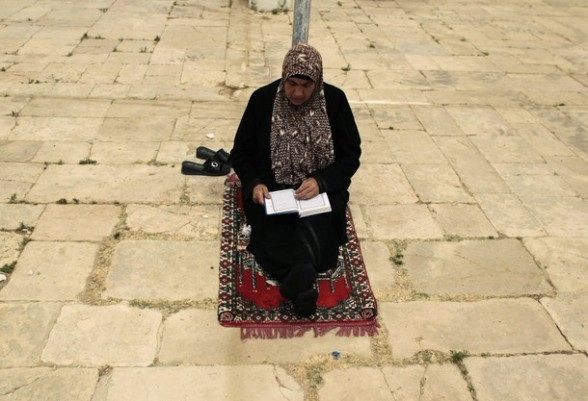 A Palestinian woman reads the Koran on the compound known to Muslims as Noble Sanctuary and to Jews as Temple Mount in Jerusalem's Old City on the first Friday of the holy month of Ramadan July 20, 2012. Israeli police said that Palestinian males over the age of 40 would be freely permitted to enter the compound in Jerusalem's Old City on Friday. REUTERS/Ammar Awad