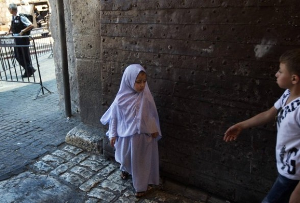 A Palestinian girl stands at Lion's Gate in Jerusalem's Old City before the first Friday of the holy month of Ramadan July 20, 2012. Israeli police said that Palestinian males over the age of 40 would be freely permitted to enter the compound known to Muslims as Noble Sanctuary and to Jews as Temple Mount in Jerusalem's Old City on Friday. REUTERS/Ronen Zvulun