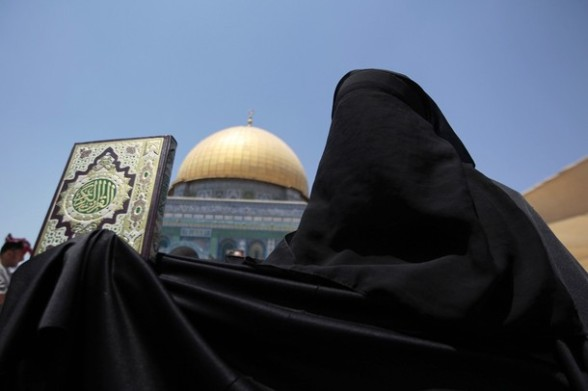 A Palestinian woman holds the Koran as she protests against Syrian President Bashar al-Assad in front the Dome of the Rock on the compound known to Muslims as Noble Sanctuary and to Jews as Temple Mount in Jerusalem's Old City on the first Friday of the holy month of Ramadan July 20, 2012. Israeli police said that Palestinian males over the age of 40 would be freely permitted to enter the compound in Jerusalem's Old City on Friday. REUTERS/Ammar Awad