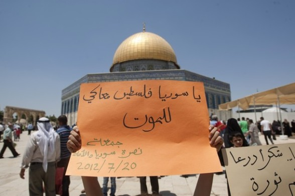 A Palestinian child holds up a sign reading in Arabic, ?Syria, Palestine is with you until the death?, during a protest outside the Dome of the Rock mosque in the al-Aqsa mosque compound in Jerusalem on July 20, 2012. AFP PHOTO/AHMAD GHARABLI