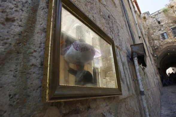 A Palestinian woman is reflected in a mirror as she carries dried sage leaves in Jerusalem's Old City on the first Friday of the holy month of Ramadan July 20, 2012. Israeli police said that Palestinian males over the age of 40 would be freely permitted to enter the compound known to Muslims as Noble Sanctuary and to Jews as Temple Mount in Jerusalem's Old City on Friday. REUTERS/Ronen Zvulun