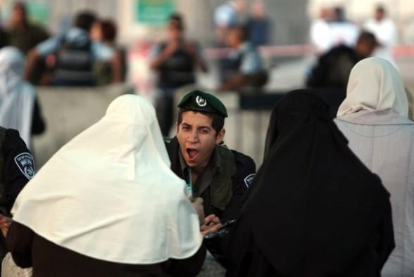 An Israeli soldier yawns as Palestinian Muslim women walk towards the Israeli checkpoint of Qalandia near the West Bank city of Ramallah before crossing on July 20, 2012, into Jerusalem to attend the first Friday prayers of the holy month of Ramadan at the Al-Aqsa mosque compound. Israeli police deployed in force in the holy city after limiting access to the compound.  AFP PHOTO/ABBAS MOMANI