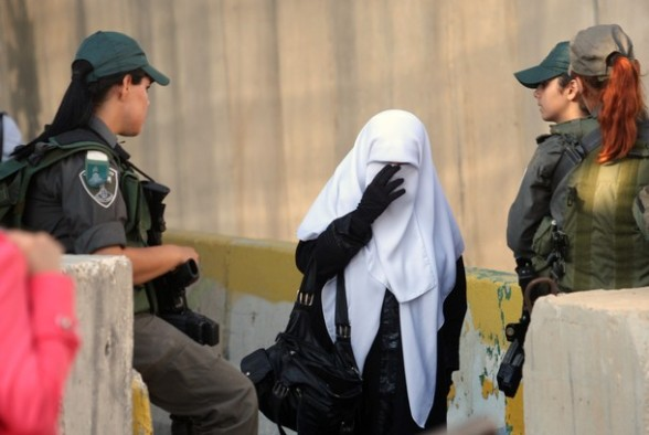 A Palestinian Muslim woman walks past Israeli soldiers maning a barricaded on the outskirts of the West Bank city of Bethlehem, on July 20, 2012, as she makes her way to Jerusalem to attend the first Friday prayers of the holy fasting month of Ramadan at the Al-Aqsa mosque compound. AFP PHOTO/MUSA AL SHAER