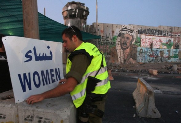 An Israeli soldier sets-up a sign directing women into the correct queue at the Israeli checkpoint of Qalandia near the West Bank city of Ramallah before crossing on July 20, 2012, into Jerusalem to attend the first Friday prayers of the holy month of Ramadan at the Al-Aqsa mosque compound. Israeli police deployed in force in the holy city after limiting access to the compound.  AFP PHOTO/ABBAS MOMANI