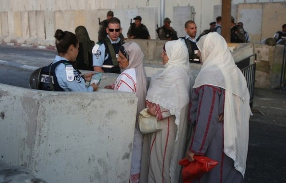 An Israeli police officer checks the ID of Muslim Palestinian women at the Qalandia checkpoint near the West Bank city of Ramallah on July 20, 2012, as worshipers head to Jerusalem to attend the first Friday prayers of the holy month of Ramadan at the Al-Aqsa mosque compound.   AFP PHOTO/ABBAS MOMANI