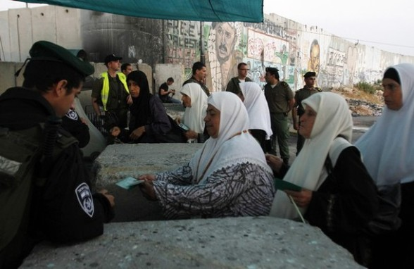 Palestinian women show their identity cards to Israeli security officers as they cross into Jerusalem at Israel's Qalandiya checkpoint outside the West Bank city of Ramallah, on the first Friday of the holy month of Ramadan July 20, 2012. REUTERS/Mohamad Torokman