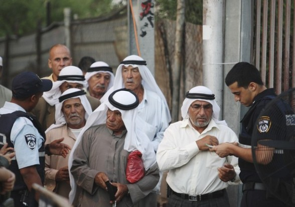 Palestinians show their identity cards at an Israeli checkpoint in Bethlehem on their way to the Al Aqsa mosque in Jerusalem on the first day of the Muslim holy month of Ramadan, Friday, July 20, 2012. Muslims from Morocco to Afghanistan are steeling themselves for the toughest Ramadan in more than three decades with no food or drink, not even a sip of water, for 14 hours a day during the hottest time of the year. (AP Photo/Nasser Shiyoukhi)