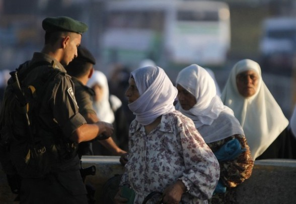 An Israeli border policeman checks the identity of Palestinian women as they cross into Jerusalem at Israel's Qalandiya checkpoint outside the West Bank city of Ramallah, on the first Friday of the holy month of Ramadan July 20, 2012. REUTERS/Mohamad Torokman