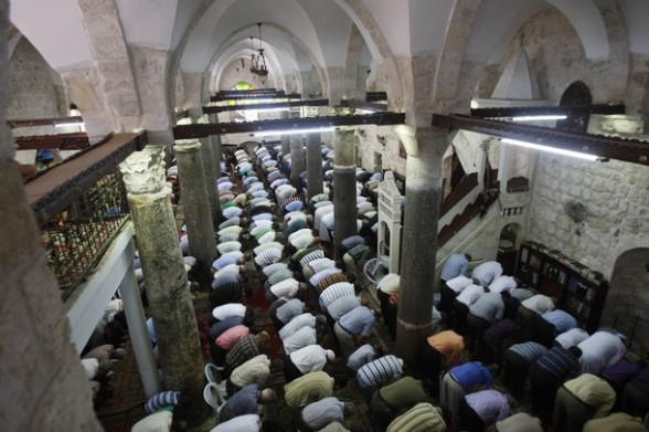 Palestinian men pray on the first Friday of the holy month of Ramadan in the West Bank city of Nablus July 20, 2012. REUTERS/Abed Omar Qusini