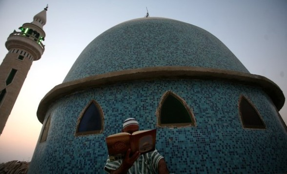 A Palestinian man reads the Koran outside a mosque in the West Bank city of Jenin on the first day of the Muslim holy fasting month of Ramadan on July 20, 2012.  AFP PHOTO / SAIF DAHLAH
