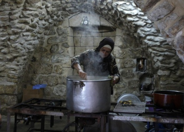 A Palestinian woman stirs a pot of rice as she prepares food to be distributed to the poor in a soup kitchen in the West Bank city of Nablus, during the Muslim holy month of Ramadan July 25, 2012. REUTERS/Abed Omar Qusini