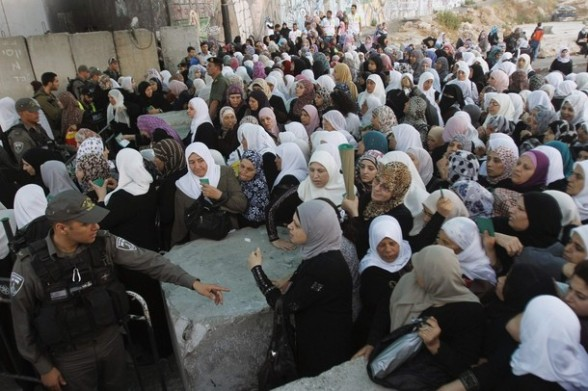 Palestinian women wait to show their identity cards to Israeli security officers at Qalandiya checkpoint outside the West Bank city of Ramallah July 27, 2012, as they make their way to Jerusalem on the second Friday of the holy month of Ramadan. REUTERS/Mohamad Torokman
