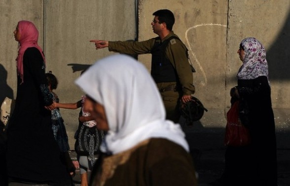 An Israeli border policeman gives instructions to Palestinian women at the Qalandia checkpoint near the West Bank city of Ramallah on July 27, 2012 as Palestinian Muslims cross into Jerusalem to attend the second Friday prayers of the fasting month of Ramadan at the Al-Aqsa mosque compound. AFP PHOTO / ABBAS MOMANI