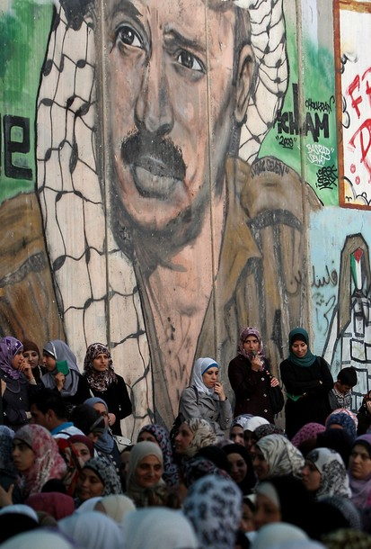 Palestinian women stand in front of a mural of late Palestinian leader Yasser Arafat painted on a section of Israel's controversial separation barrier as they wait to cross into Jerusalem from the Qalandia checkpoint near the West Bank city of Ramallah on July 27, 2012. Palestinian Muslims are heading to Jerusalem to attend the second Friday prayers of the fasting month of Ramadan at the Al-Aqsa mosque compound. AFP PHOTO / ABBAS MOMANI