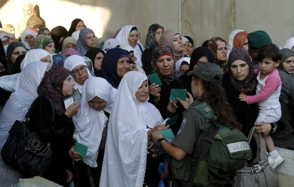 Palestinian women show their ID cards to an Israeli border policewoman as they wait to cross into Jerusalem from the West Bank city of Bethlehem on July 27, 2012. Palestinian Muslims are heading to Jerusalem to attend the second Friday prayers of the fasting month of Ramadan at the Al-Aqsa mosque compound. AFP PHOTO / MUSA AL-SHAER