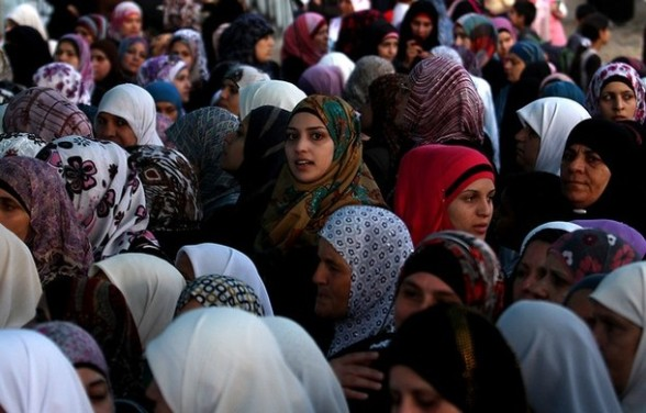 Palestinian women wait to cross into Jerusalem from the Qalandia checkpoint near the West Bank city of Ramallah on July 27, 2012. Palestinian Muslims are heading to Jerusalem to attend the second Friday prayers of the fasting month of Ramadan at the Al-Aqsa mosque compound. AFP PHOTO / ABBAS MOMANI